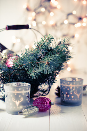 Vintage Christmas decor, old Christmas decorations, lanterns, garlands and spruce branches on a white table. Retro colors photo