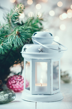 Vintage Christmas decor, old Christmas decorations, lanterns, garlands and spruce branches on a white table. photo