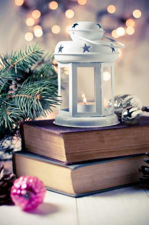 Vintage Christmas decor, old Christmas decorations, lanterns, garlands and spruce branches on a stack of books photo