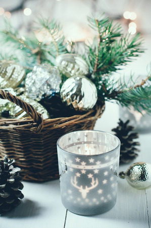 Vintage Christmas decor, old Christmas decorations in a basket, lanterns, garlands and spruce branches on a white table. photo
