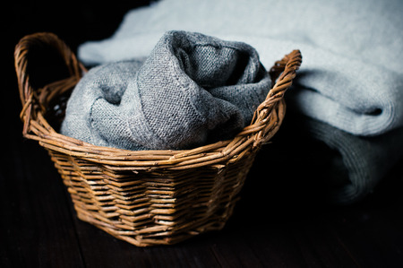 Fabric, gray knitted blanket in a wicker basket and cozy winter sweaters on a black background