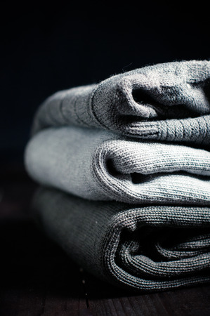 cold storage: A stack of gray knitted winter sweaters on a dark background