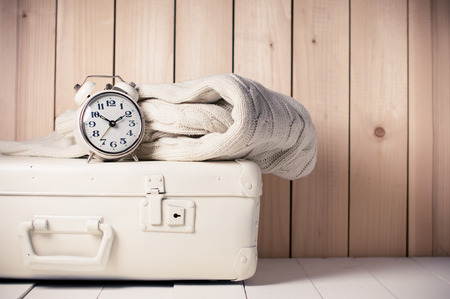 Beige knitted sweater, alarm clock and vintage suitcase on wooden background, retro decor