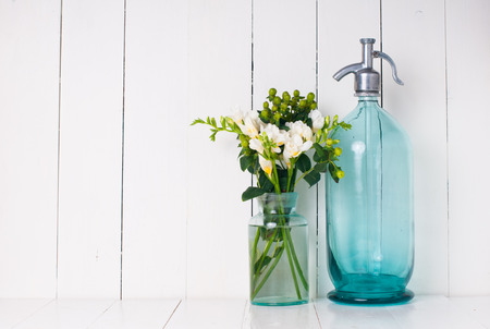 Vintage home decor, ancient turquoise siphon, freesias bouquet and bottles on a white wooden background. photo