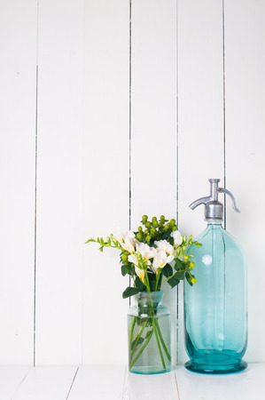 siphon: Vintage home decor, ancient turquoise siphon, freesias bouquet and bottles on a white wooden background.