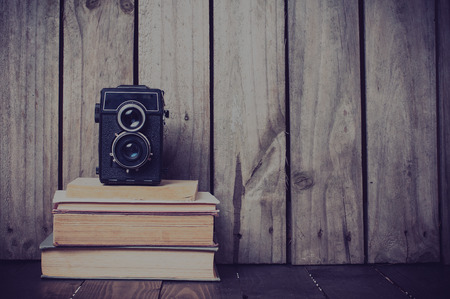 Vintage medium format camera and a stack of books on a wooden board, hipster style photo