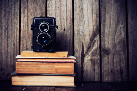 Vintage medium format camera and a stack of books on a wooden board, grunge style photo