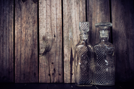 carafe: Two vintage glass bottles, decanters for alcoholic drinks on a wooden board, grunge style