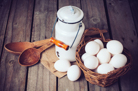 country kitchen: Country kitchen Still Life, enamel milk can, eggs in a wicker basket and wooden spoons on a background of the old board, vintage style