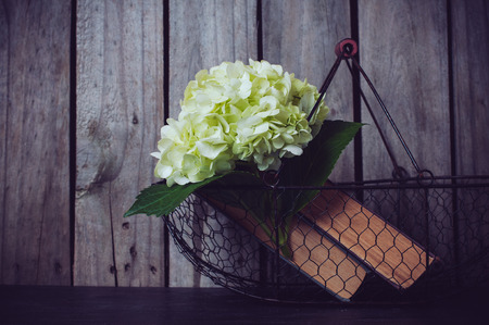 White hydrangea flowers and vintage books in a metal basket on a wooden background. Фото со стока