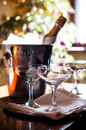 Luxury holiday composition, a bottle of chilled champagne in an ice bucket and vintage glasses, festive lights in the background photo
