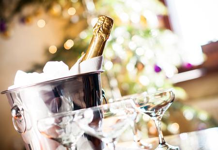 flauta: Composición de vacaciones de lujo, una botella de champaña fría en un cubo de hielo y vasos de época, las luces festivas en el fondo