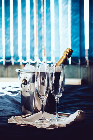 chilled: A bottle of chilled champagne in an ice bucket and two glasses on a bed, in front of window curtains.