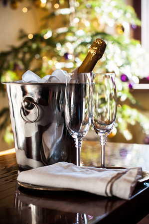 Luxury holiday table setting, a bottle of chilled champagne in an ice bucket and elegant glasses, festive lights in the background photo