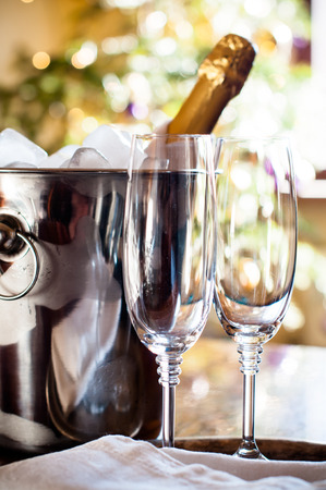 chilled: Luxury holiday table setting, a bottle of chilled champagne in an ice bucket and elegant glasses, festive lights in the background Stock Photo
