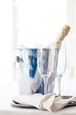 A bottle of chilled champagne in an ice bucket and two glasses on a white tablecloth, luxurious celebration, bright daylight photo