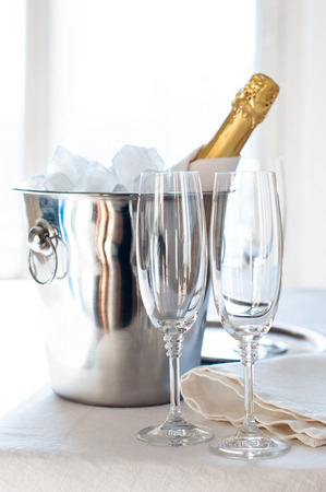 chilled: A bottle of chilled champagne in an ice bucket and two glasses on a white tablecloth, luxurious celebration, bright daylight Stock Photo