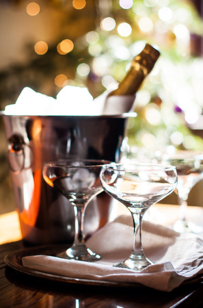 chilled: Luxury holiday composition, a bottle of chilled champagne in an ice bucket and vintage glasses, festive lights in the background