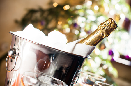 chilled: Luxurious holiday composition, a bottle of chilled champagne in an ice bucket and napkin closeup on lights background