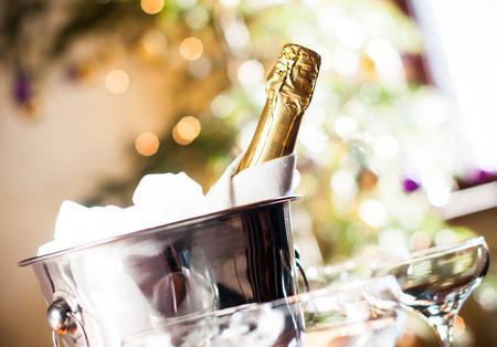 botella champagne: Composición de vacaciones de lujo, una botella de champaña fría en un cubo de hielo y servilleta de cerca sobre fondo de las luces