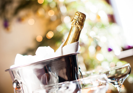champagne flute: Luxurious holiday composition, a bottle of chilled champagne in an ice bucket and napkin closeup on lights background