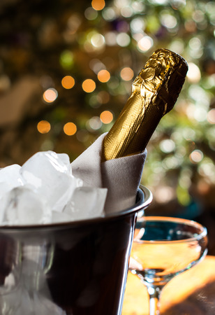 Luxurious holiday composition, a bottle of chilled champagne in an ice bucket and napkin closeup on lights background photo