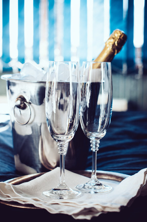 A bottle of chilled champagne in an ice bucket and two glasses on a bed, in front of window curtains. photo