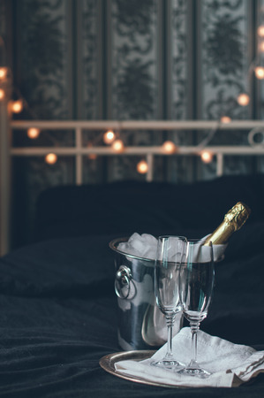 A bottle of chilled champagne in an ice bucket and two glasses on a bed, dark tones photo