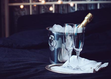 Een fles gekoelde champagne in een ijsemmer en twee glazen op een bed, donkere tinten Stockfoto