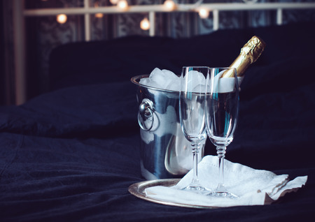 A bottle of chilled champagne in an ice bucket and two glasses on a bed, dark tones Standard-Bild