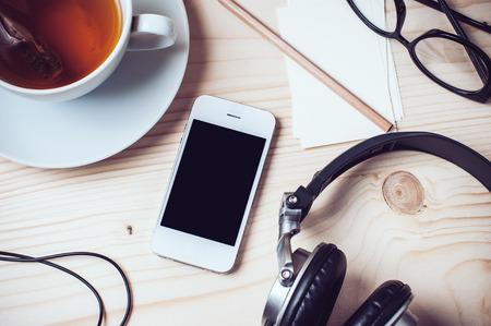 紙レコード、ティー、携帯電話、ヘッドフォン、めがね、木製オフィス デスクトップ、流行に敏感なスタイルの鉛筆のカップ 写真素材