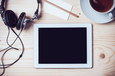 Los registros en papel, taza de té, tablet, auriculares, gafas y un lápiz en el escritorio de oficina de madera, estilo inconformista Foto de archivo