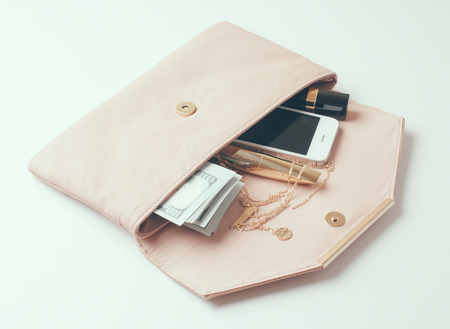Cosmetics, jewelry, money and smartphone in an open beige womans clutch handbag on a white background. Banco de Imagens