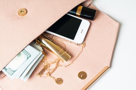 Cosméticos, joyas, dinero y el teléfono inteligente en el bolso de embrague de una mujer de color beige abierta sobre un fondo blanco.