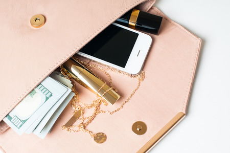 Cosmetics, jewelry, money and smartphone in an open beige womans clutch handbag on a white background. Stock Photo