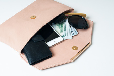 Cosmetics, sunglasses, money, purse and smartphone in an open beige womans clutch handbag on a white background.