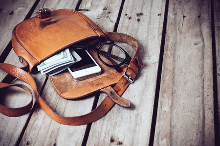 closeup on bags: Optical glasses, money and smartphone in an open leather hipsters bag on a wooden board background. Stock Photo