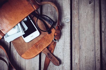 Optical glasses, money and smartphone in an open leather hipster's bag on a wooden board background.