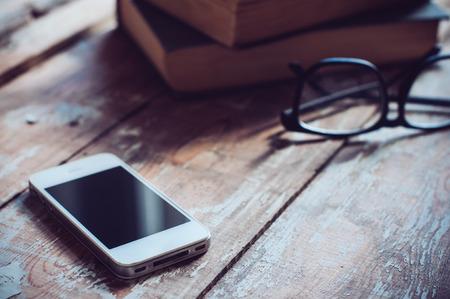 Vieux livres anciens, smartphones et des verres sur une table en bois