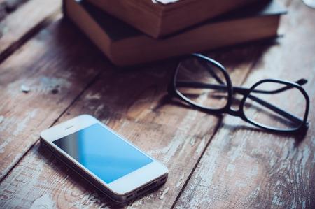 Stare zabytkowe książki, smartfon i szklanki na drewnianym stole
