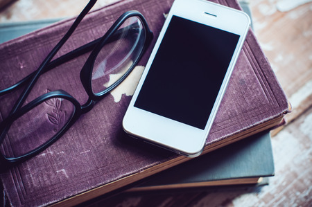 telefono antico: Vecchi libri dell'annata, smartphone e bicchieri su un tavolo di legno
