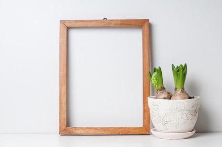 Giacinto e narciso germogli in vasi di ceramica e vuota cornice di legno su un muro bianco Archivio Fotografico