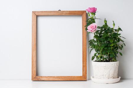 Vintage lege houten frame en roos in een pot op een witte muur Stockfoto