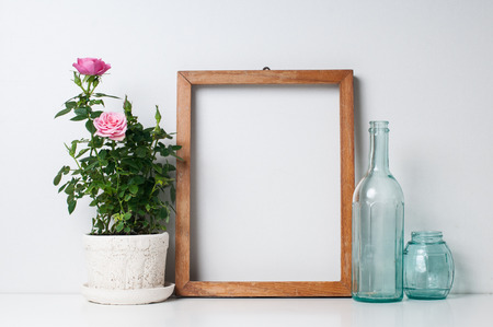 Vintage blank wooden frame, bottles and rose in a pot on a white wall Standard-Bild