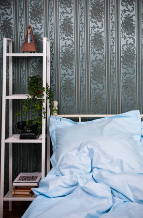 double bed: Cozy bedroom interior, double bed with light blue bed linen, pillows and shelves with vintage decor Stock Photo