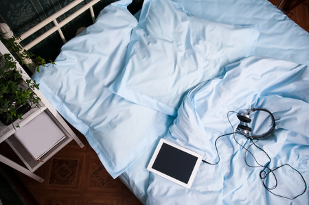 Knusse slaapkamer interieur, dubbel bed met lichtblauwe beddengoed, kussens, tablet met een koptelefoon en planken met vintage decor, schot van boven
