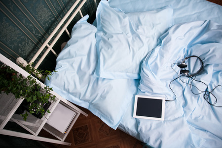 view of a comfortable bedroom: Cozy bedroom interior, double bed with light blue bed linen, pillows, tablet with headphones and shelves with vintage decor, shot from above Stock Photo