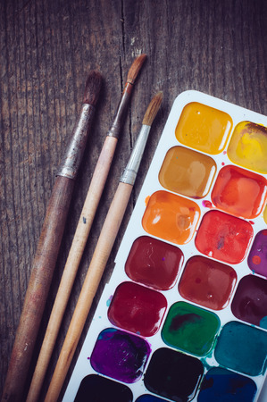 paint box: Watercolor paints and brushes, painting tools on an old wooden board. Stock Photo