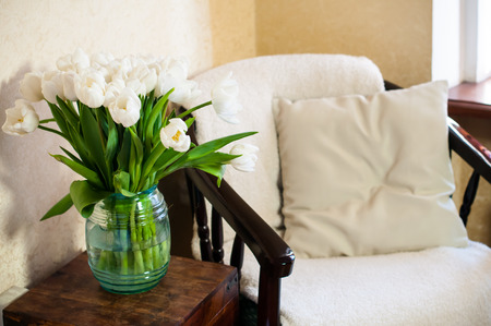 vintage chair: Home interior, vintage chair with a pillow and a bouquet of white tulips