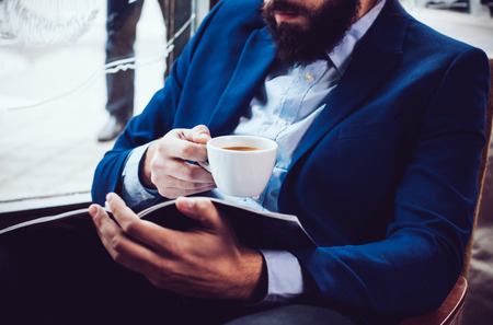 magazine: Young businessman in a blue jacket with a cup of coffee, reading a magazine in a cafe